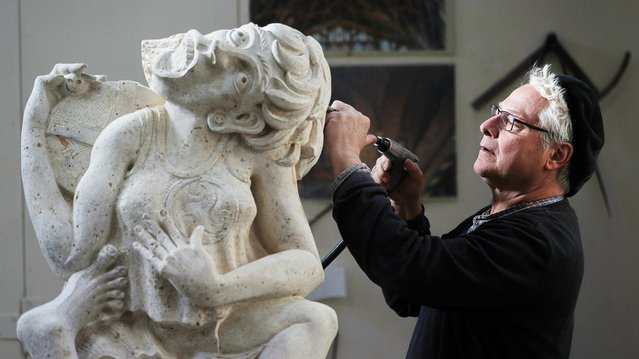 Master mason Pascal Mychalysin works on a gargoyle holding a cheese on October 15, 2020, to represent the Cheese Rollers of Gloucestershire, as part of a project for Gloucester Cathedral to depict local areas in a more modern way. (Photo by David Davies/PA Images via Getty Images)