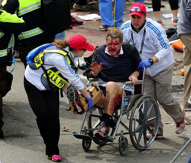 Medical workers aid an injured man following the explosions. (Photo by David L. Ryan/The Boston Globe)