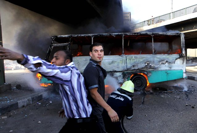 """A man calls for help to extinguish a fire reported to be set by black block protesters on a bus belonging to Muslim Brotherhood supporters in Cairo, on April 19, 2013. Several hundred supporters and opponents of Egypt's President Mohammed Morsi clashed near Cairo's Tahrir Square amid a rally calling on Morsi to """"cleanse the judiciary"""". (Photo by Amr Nabil/Asociated Press)"""