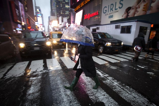 A woman crosses a street in Times Square under the pouring rain, in New York December 9, 2014. (Photo by Carlo Allegri/Reuters)