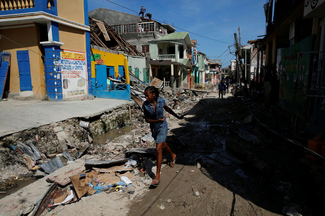 A woman runs on a street filled with rubble and past damaged houses after Hurricane Matthew passes in Jeremie, Haiti, October 8, 2016. (Photo by Carlos Garcia Rawlins/Reuters)