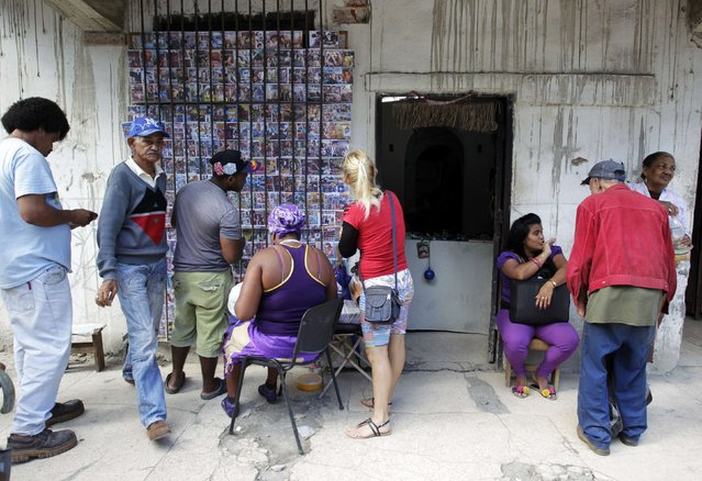 Cubans look at pirated DVDs for sale at a street stall in Havana December 17, 2014. (Photo by Reuters/Stringer)