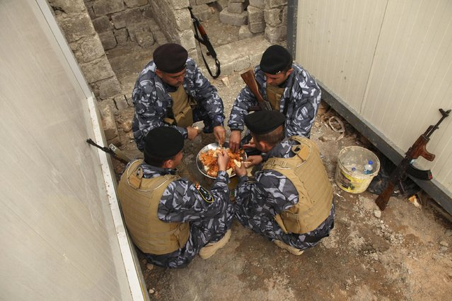 Sunni volunteers, who have joined the Iraqi army to fight against militants of the Islamic State, share a meal on the outskirts of Dohuk province December 8, 2014. (Photo by Ari Jalal/Reuters)