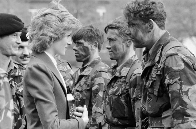 Princess Diana talks with camouflaged-colored combat soldiers when she inspected her Royal Hampshire Regiment in West Berlin on Saturday, October 19, 1985. Princess Diana is a Colonel-in-Chief of the Berlin-based regiment. She holds a box of chocolate and a red rose she was presented with. (Photo by Heribert Proepper/AP Photo)