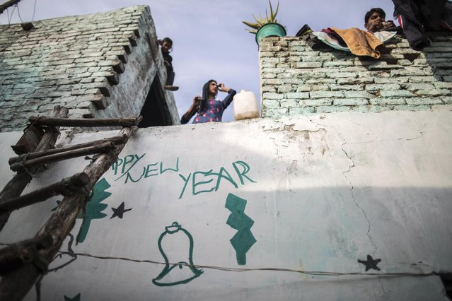 A Christian family is seen atop of their house ahead of Christmas in a Christian slum in Islamabad December 24, 2014. (Photo by Zohra Bensemra/Reuters)