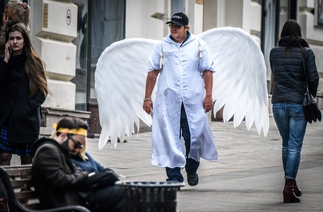 A man with angel wings walks through downtown Moscow on April 6, 2018, in celebration of the Russian Orthodox Easter holiday. The Russian Orthodox Church celebrates Easter on April 8. (Photo by Mladen Antonov/AFP Photo)