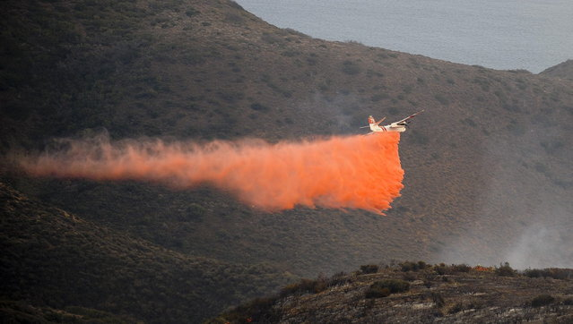 A air tanker drops fire retardant on the Springs Fire near Malibu, California May 3, 2013. A fierce, wind-whipped wildfire spread on Friday along the California coast northwest of Los Angeles, threatening 4,000 homes and a military base as residents were evacuated ahead of the flames and a university campus was closed. (Photo by Gus Ruelas/Reuters)