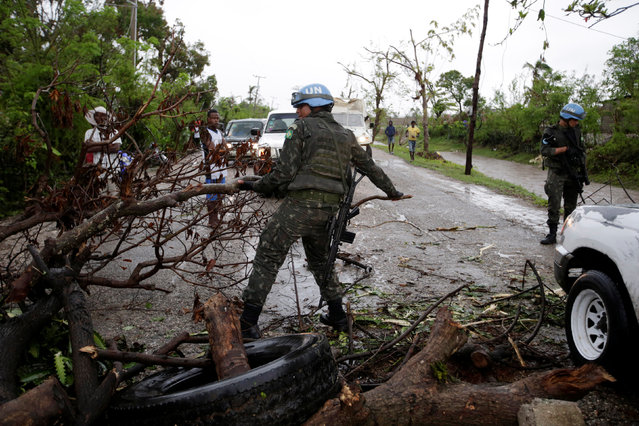A Brazilian peacekeeper clears part of a barricade set up by residents to protest and demand aid for their neighborhood after Hurricane Matthew in Les Cayes, Haiti, October 21, 2016. (Photo by Andres Martinez Casares/Reuters)