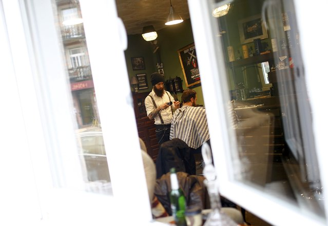 "Alex ""Torreto"" Vellios, a 26-year old Greek-born barber is pictured through the window of his Torreto barber shop in the basement of a ordinary residential property in Frankfurt January 6, 2015. (Photo by Kai Pfaffenbach/Reuters)"