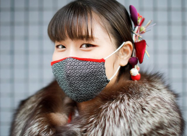 A Kimono-clad woman wearing a fashionable face mask poses for a photograph at Coming of Age Day celebration ceremony at Yokohama Arena after the government declared the second state of emergency for the capital and some prefectures, amid the coronavirus disease (COVID-19) outbreak, in Yokohama, south of Tokyo, Japan on January 11, 2021. On the second Monday in January every year, people who have turned or are about to turn 20 take part in ceremonies in local event halls or other large-scale venues to celebrate the rite of passage to adulthood. The occasion, which is observed with a national holiday, serves in effect as class reunions for some and represents one of the major child-rearing milestones for parents. (Photo by Issei Kato/Reuters)