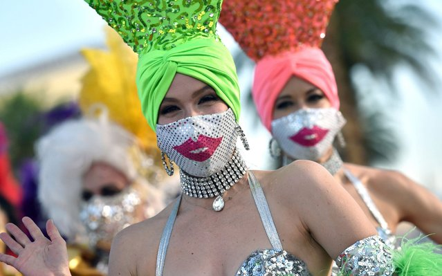 """Models dressed as showgirls participates in a fashion show in front of the Welcome to Fabulous Las Vegas sign on the Las Vegas Strip to kick off the pro-mask wearing campaign """"Mask Up for Nevada"""" put on by Experience Strategy Associates amid the spread of the coronavirus on June 25, 2020 in Las Vegas, Nevada. On Wednesday, Nevada Gov. Steve Sisolak signed a directive requiring people to wear face coverings in public places throughout the state beginning on June 26 in response to a four-week upward trend of new daily COVID-19 cases. (Photo by David Becker/Zuma Press)"""