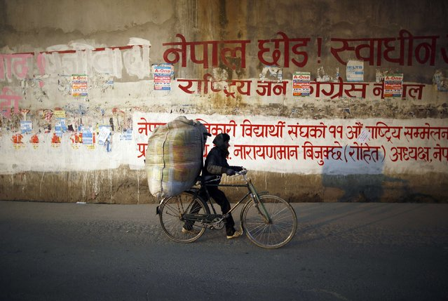 A man carrying goods on his bicycle walks along the deserted road during the general strike independently called by the Unified Communist Party of Nepal (Maoist) and led by 30 party alliance and the Communist Party of Nepal (Maoist), demanding that the drafting of the new constitution is done on time through consensus, in Kathmandu January 13, 2015. (Photo by Navesh Chitrakar/Reuters)