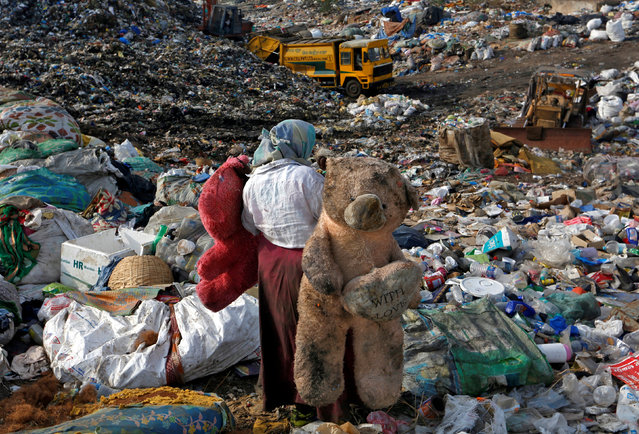 A woman carries stuffed toys through a dump site on the outskirts of Mumbai, India, June 4, 2018. (Photo by Francis Mascarenhas/Reuters)