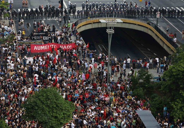 Demonstrators march in front of a line of riot police during a protest against fare hikes for city buses, subway and trains in Sao Paulo January 16, 2015. Brazilian police fired tear gas to disperse hundreds of people protesting an increase in transit fares in Sao Paulo, the country's biggest city, on Friday, raising fears of more disruption after a similar demonstration turned violent last week. (Photo by Nacho Doce/Reuters)