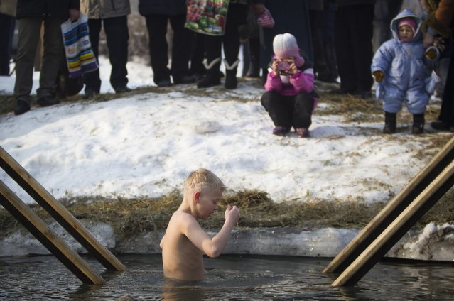 A boy bathes in the icy water of the Bolshaya Almatinka river during an Epiphany celebration in Almaty January 19, 2015. (Photo by Shamil Zhumatov/Reuters)
