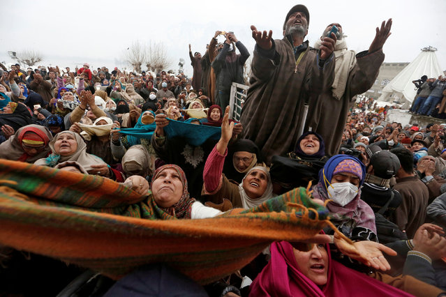 Kashmiri Muslims react upon seeing a relic believed to be hair from the beard of Prophet Mohammed, being displayed during a festival to mark the death anniversary of Abu Bakr, one of the companions of Prophet Mohammad, at the Hazratbal shrine in Srinagar, February 5, 2021. (Photo by Danish Ismail/Reuters)