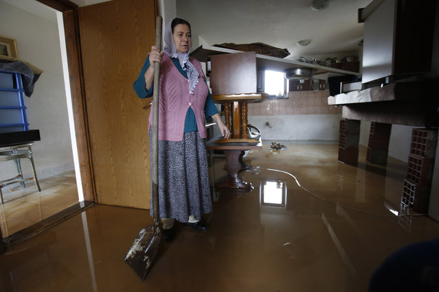 Bosnian Ibrema Avdic, 56, stands in floodwaters in her home in the Sarajevo suburb of Osijek, Bosnia, Tuesday, January 20, 2015. Heavy overnight rainfall caused rivers to rise in the Sarajevo area on Monday and flood homes in the suburbs for the fifth time in the past 20 months. Residents said that over the past few years their homes have been flooded two or three times annually. (Photo by Amel Emric/AP Photo)
