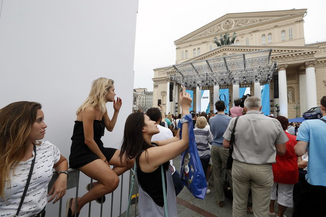 People enjoy The Bolshoi Theater's orchestra concert Opera without borders, a worldwide project by BMW, in front of the theater at Teatralnaya square in Moscow, 24 June 2018. Chief conductor of the Bolshoi, Tugan Sokhiyev, soloists of the theater Oleg Dolgov, Igor Golovatenko, Anna Bondarevskaya, Anna Aglatova and Bogdan Volkov performed arias from the repertoire of the Bolshoi. The concert was free of charge and attcacted many tourists and soccer fans. (Photo by Sergei Chirikov/EPA/EFE)