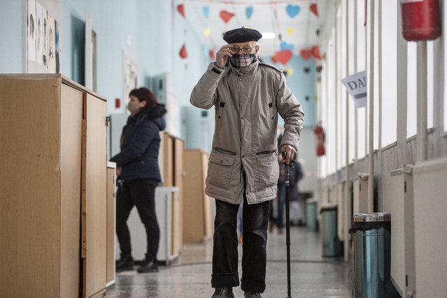 An old man arrives at the polling station to cast his ballot in parliamentary elections in capital Pristina, Kosovo on Sunday, February 14, 2021. Kosovo is holding an early parliamentary election to form a new government amid the coronavirus pandemic, an economic downturn and stalled negotiations with wartime foe Serbia. Some 1.8 million eligible voters on Sunday started to cast their ballots in 2,400 polling stations. They're electing 120 lawmakers among more than 1,000 candidates from 28 political groupings. (Photo by Visar Kryeziu/AP Photo)