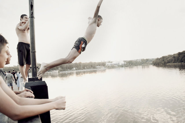 Young boys jump from a bridge a few kilometres from the front line. (Photo by Aude Osnowycz/The Guardian)