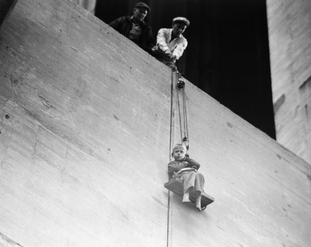 Ronald Hughes, 8, starts his descent from a lofty perch atop a 100- foot bridge pier in Pittsburgh, Pa., July 6, 1954. He is lowered in a boatswain's chair after being rescued by a pair of veteran bridge painters. Ronald and his six-year-old brother spent the entire night in a precarious position after climbing up on a catwalk.The boys were cold and dirty, but uninjured. (Photo by AP Photo)