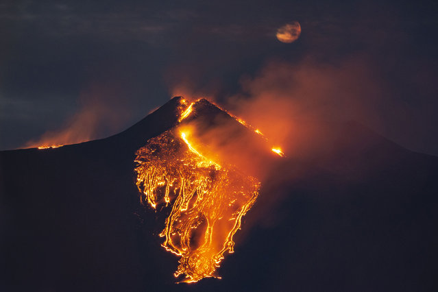 The moon is partially seen in the sky as lava flows from the Mt Etna volcano, near Catania in Sicily, southern Italy, early Tuesday, February 23 , 2021. The explosion started before midnight on Monday night, provoking a huge eruption plume that rose for several kilometers from the top of Etna, as reported by The National Institute of Geophysics and Volcanology, Etneo Observatory. (Photo by Salvatore Allegra/AP Photo)