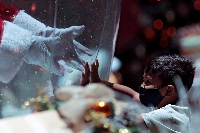 Abilio da Cruz Pinto, 77, dressed as a Santa Claus inside a plastic bubble, greets a child in a shopping mall amid the coronavirus disease (COVID-19) outbreak in Brasilia, Brazil on December 15, 2020. (Photo by Adriano Machado/Reuters)