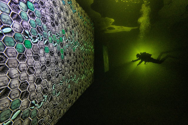 A diver uses a torch to explore artworks under the ice of the White Sea off the coast of the Republic of Karelia, Russia on February 26, 2021. Paintings and sculptures by artist Denis Lotarev and works by photographer Viktor Lyagushkin are placed under the water and accessible to divers until the ice melts. Picture taken February 26, 2021. (Photo by Viktor Lyagushkin/Handout via Reuters)