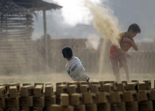 Boys play at a brick kiln on the outskirts of Yangon February 1, 2015. (Photo by Soe Zeya Tun/Reuters)