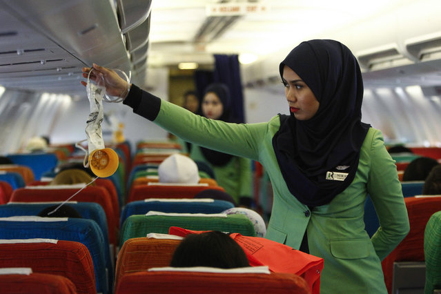 In this December 22, 2015, photo, a Rayani Air flight crew demonstrates a safety brief before departure at the Sultan Ismail Petra Airport in Kelantan, Malaysia. (Photo by Joshua Paul/AP Photo)
