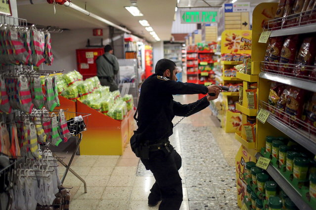 An Israeli policeman searches a supermarket inside the Central Jerusalem Bus Station after police said a woman was stabbed by a Palestinian outside the bus station October 14, 2015. A Palestinian stabbed and moderately wounded a 70-year-old woman outside Jerusalem's central bus station, at the entrance to the city, before an officer shot him dead, a police spokeswoman said. (Photo by Noam Moskowitz/Reuters)