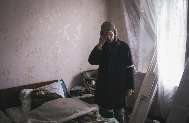 An elderly man stands next to the body of his wife, who died of an apparent heart attack after an ambulance was unable to make its way through fighting, in the town of Vuhlehirsk, eastern Ukraine, Tuesday, February 10, 2015. Fighting in eastern Ukraine intensified on Tuesday ahead of much-anticipated peace talks, with both sides claiming significant advances. (Photo by Vadim Braydov/AP Photo)