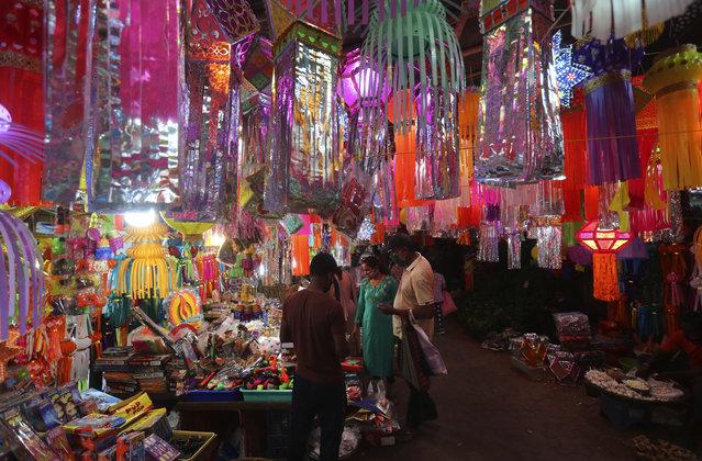 Indian shops for lanterns at a roadside stall ahead of Diwali, the Hindu festival of lights, in Mumbai, India, Saturday, November 7, 2020. Diwali will be celebrated on Nov. 14. (Photo by Rafiq Maqbool/AP Photo)