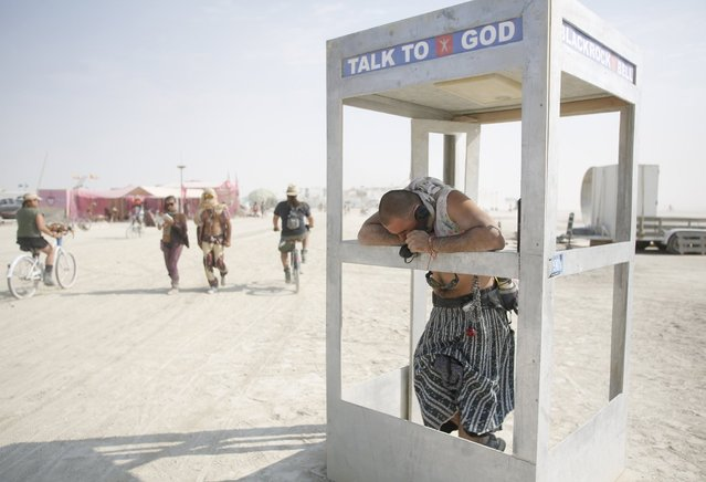 Pippin, his Playa name, chats on the phone with God during the Burning Man 2013 arts and music festival in the Black Rock Desert of Nevada, September 1, 2013. The federal government issued a permit for 68,000 people from all over the world to gather at the sold out festival, which is celebrating its 27th year, to spend a week in the remote desert cut off from much of the outside world to experience art, music and the unique community that develops. (Photo by Jim Urquhart/Reuters)