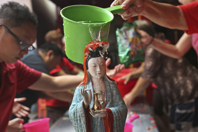 A Chinese god statue is cleaned by an Indonesian of Chinese descent in preparation for the Lunar New Year celebration at a temple in the China Town in Jakarta, Indonesia, Thursday, February 12, 2015. Chinese communities in the world's most populous Muslim country are gearing up to celebrate the start of the year of the goat which falls on Feb. 19. (Photo by Tatan Syuflana/AP Photo)