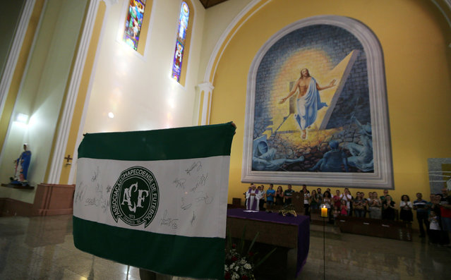 A fan of Chapecoense soccer team holds a flag of her team during a mass at the Santo Antonio Cathedral in Chapeco, Brazil, November 29, 2016. (Photo by Paulo Whitaker/Reuters)