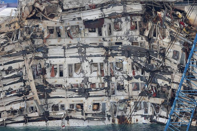 "A detail of the previously submerged side of the Costa Concordia is seen after it was lifted upright, on the Tuscan Island of Giglio, Italy, Tuesday, September 17, 2013. The crippled cruise ship was pulled completely upright early Tuesday after a complicated, 19-hour operation to wrench it from its side where it capsized last year off Tuscany, with officials declaring it a ""perfect"" end to a daring and unprecedented engineering feat. (Photo by Andrea Sinibaldi/AP Photo/Lapresse)"