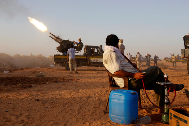 An anti-Gaddafi fighter tests an anti-aircraft gun southwest of Sirte, Libya one of Muammar Gaddafi's last remaining strongholds, September 16, 2011. (Photo by Goran Tomasevic/Reuters)