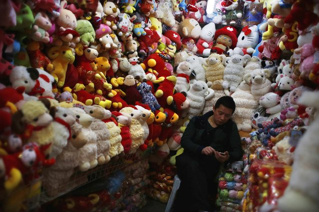 A vendor, selling traditional decorations for the upcoming Chinese Lunar New Year, looks at his mobile phone as he waits for customers at a shopping area in downtown Shanghai, February 12, 2015. (Photo by Carlos Barria/Reuters)
