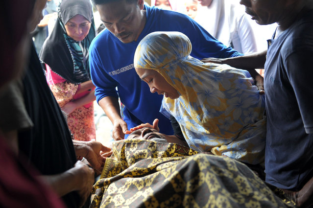 A woman grieves for her relative who died after an earthquake in Pidie Jaya, Aceh province on December 7, 2016. (Photo by Chaideer Mahyuddin/AFP Photo)