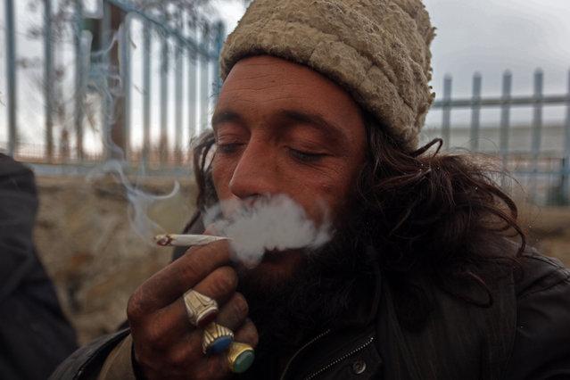 An Afghan man smokes hashish in Kabul, Afghanistan, Sunday, January 25, 2015. (Photo by Rahmat Gul/AP Photo)