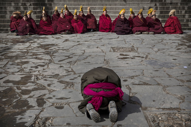 A worshipper prays in front of Tibetan Buddhist monks during Monlam or the Great Prayer rituals on March 5, 2015 at the Labrang Monastery, Xiahe County, Amdo, Tibetan Autonomous Prefecture, Gansu Province, China. (Photo by Kevin Frayer/Getty Images)