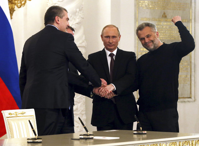 Russian President Vladimir Putin (2nd R), Crimea's Prime Minister Sergei Aksyonov (front L), Crimean parliamentary speaker Vladimir Konstantinov (back L) and Sevastopol Mayor Alexei Chaliy shake hands after a signing ceremony at the Kremlin in Moscow March 18, 2014. (Photo by Sergei Ilnitsky/Reuters)