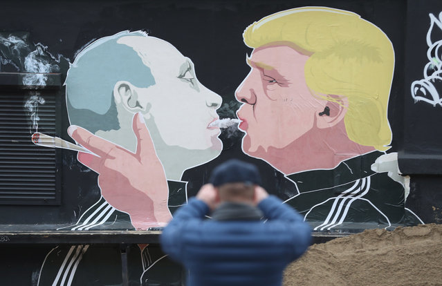 A passerby photographs a mural showing U.S. President-elect Donald Trump (R) blowing marijuana smoke into the mouth of Russian President Vladimir Putin on the wall of a bar-b-que restaurant on November 23, 2016 in Vilnius, Lithuania. Many people in the three Baltic nations of Lithuania, Latvia and Estonia are concerned that Russia, because Trump has expressed both admiration for Putin and doubt over defending NATO member states, will be emboldened to intervene militarily in the Baltics. (Photo by Sean Gallup/Getty Images)