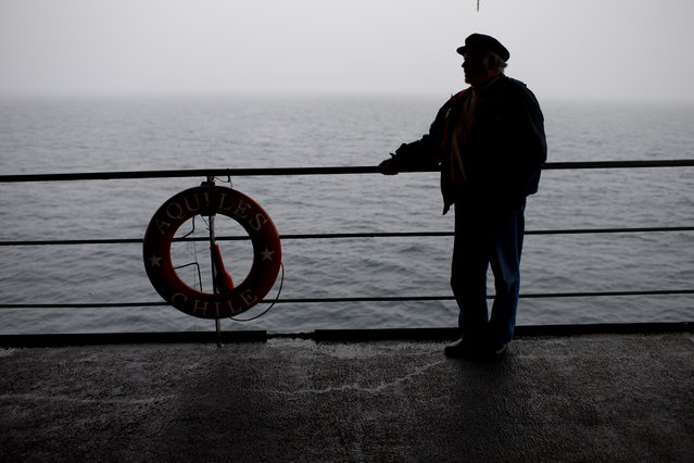 """In this January 25, 2015 photo, tourist Juan Enrique Kemp stands aboard The Aquiles, a Chilean Navy icebreaker, near Byers Peninsula, Livingston Island, in the South Shetland Islands archipelago, Antarctica. """"In Antarctica, you can plan all you like, but you can't really schedule anything"""", goes a local saying. (Photo by Natacha Pisarenko/AP Photo)"""