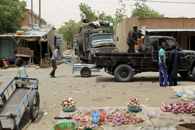Soldiers stop to buy goods at the main market of Diffa, Niger, March 23, 2015. (Photo by Joe Penney/Reuters)