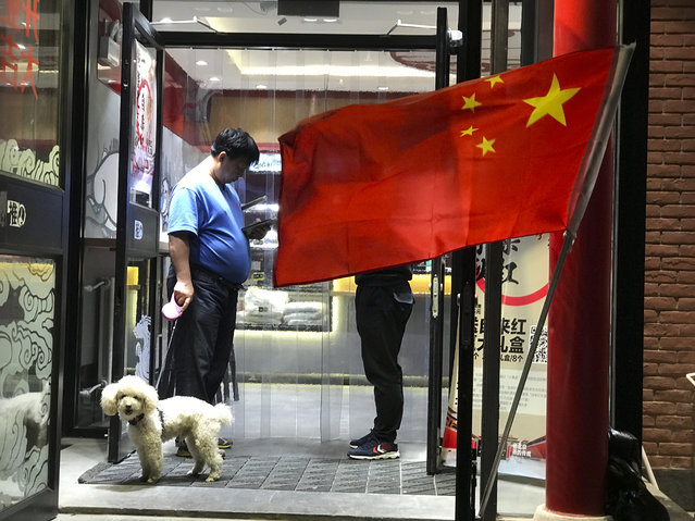 In this October 3, 2017, file photo, a man walks his dog as he leaves a restaurant flying the Chinese national flag in Beijing, China. A city in southwestern China has banned dog walking during the daytime and banished the pets entirely from parks, shopping centers, sports facilities, and other public spaces. (Photo by Ng Han Guan/AP Photo)