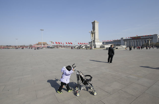 A tourist girl pulls on her buggy at the Tiananmen Square on the eve of the Chinese Lunar New Year, in Beijing, China, February 7, 2016. (Photo by Jason Lee/Reuters)