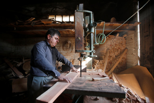 Palestinian Yahiya Idress, who makes decorative objects from olive wood to be sold as souvenirs, works in his workshop in the west Bank city of Hebron November 22, 2016. (Photo by Mussa Qawasma/Reuters)