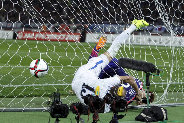 Japan's Shinji Okazaki (R) and Uzbekistan's Lutfulla Turaev dive into the net after Japan's Gaku Shibasaki (not in picture) scored during their international friendly soccer match in Tokyo March 31, 2015. (Photo by Yuya Shino/Reuters)